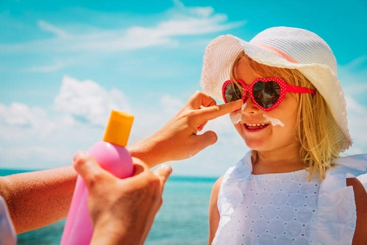 Putting sunscreen on a little girl